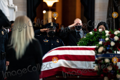 The Used Photo - United States Capitol Police officer Ken Shaver who was also injured in the April 2nd  attack at the Capitol center raises his hand in salute to the late US Capitol Police officer William Billy Evans as he lies in honor in the Rotunda of the US Capitol in Washington DC on April 13th 2020Credit Anna Moneymaker  Pool via CNPAdMedia