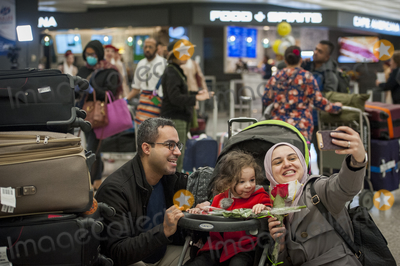 The Interns Photo - A family is united and takes a selfie as passengers arrive from Dubai after a 14-hour flight on Emirates flight 231 at the international terminal at Dulles International Airport in Dulles Va Monday March16 2020 Some people are taking the precaution of wearing face masks as they arrive to be greeted by family and or friends Credit Rod Lamkey  CNPAdMedia