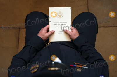 The Ceremonies Photo - WASHINGTON DC - FEBRUARY 3 A US Capitol Police Officer holds a program for the ceremony memorializing US Capitol Police Officer Brian D Sicknick 42 as he lies in honor in the Rotunda of the Capitol on Wednesday February 3 2021 Officer Sicknick was responding to the riot at the US Capitol on Wednesday January 6 2021 when he was fatally injured while physically engaging with the mob Members of Congress will pay tribute to the officer on Wednesday morning before his burial at  Arlington National Cemetery  Credit Demetrius Freeman  Pool via CNPAdMedia