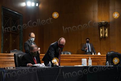 Doug Jones Photo - A staffer cleans the microphone for United States Senator Doug Jones (Democrat of Alabama) at a US Senate Health Education Labor and Pensions Committee hearing on new coronavirus tests on Capitol Hill in Washington Thursday May 7 2020Credit Anna Moneymaker  Pool via CNPAdMedia