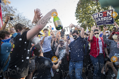 Vice President Joe Biden Photo - A woman pops open a bottle of champagne as sprays it as people celebrate in the streets near the White House in the hours after Democratic presidential candidate and former Vice President Joe Biden was elected president in Washington DC Saturday November 7 2020 Credit Rod Lamkey  CNPAdMedia