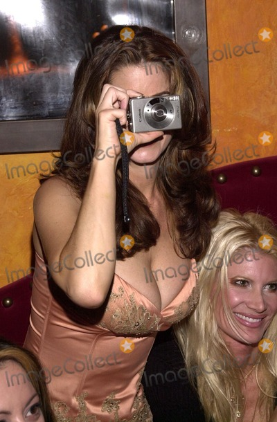 Carrie Stevens Photo - Playmate Carrie Stevens takes a picture at a Tongue Magazine party to celebrate the release of the second KISS condom Studded Paul Barfly West Hollywood CA 09-27-02