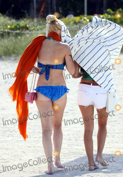 Ali Lohan Photo - After enjoying a dip in the warm ocean troubled American starlet Lindsay Lohan leaves the beach under cover with her entourage that includes younger sister Ali Lohans arm is covered in smudges from what looks like a fake tattoo which looks like it reads blood that washed off in the water and her legs show signs of cuts and scarring With her hair up Lohans hair extensions are clearly visible Miami Beach FL 52311Fees must be agreed prior to publication