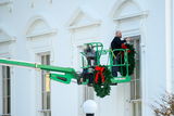 Photo - A worker hangs Christmas wreaths on the White House windows