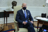 Photos From U.S. President Joe Biden wears a protective mask while speaking during a meeting on infrastructure with House members in the Oval Office of the White House in Washington